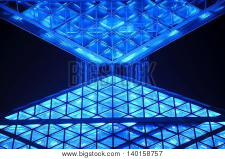 An abstract building lit up at night with blue lights in Beijing china.