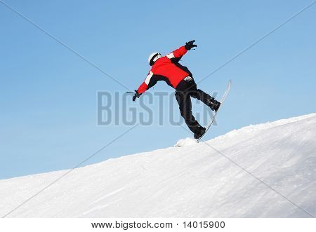 Snowboard sportsmen in jump over clear blue sky