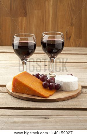 vertical image of cheese grapes and wineglass