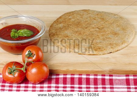 pizza dough fresh tomatoes and tomato sauce with basil leaf