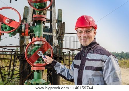 Oilfield worker repairing wellhead valve with the wrench wearing red helmet and work clothes. Oil and gas concept.