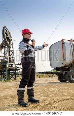 Worker talking on the radio near pump jack and tank trailer in the oilfield. Oil and gas concept.