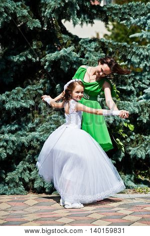 Mother And Daughter At White And Green Dress At Sunny Day