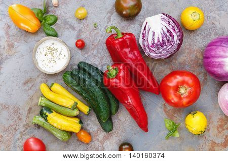 Ingredients for a colorful vegetable salad with a  spicy dressing, top view
