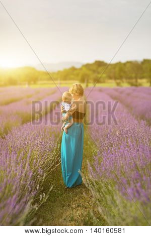 Young woman and son wearing blue dress posing in a lavender field. Concept positive mood. Selective focus on woman and son.