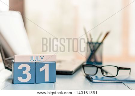 July 31st. Day 31 of month wooden color calendar on business office background. Summer time. Empty space for text.