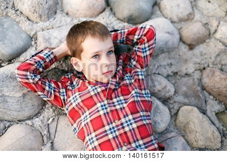 boy lying on the beach and looking at the sky. boy lies on the rocky shore and dreams. hands behind head. pensiveness. top view
