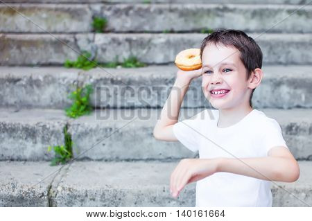 food fight. boy throws a donut and laughs. naughty children have fun when they throw food. the concept of throwing food. consumerism.