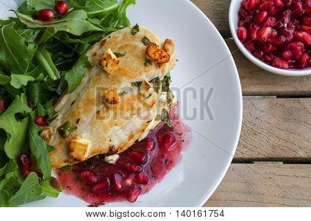 fried chicken breast fillet gratinated with feta cheese arugula salad and pomegranate sauce on a rustic wooden table top view from above