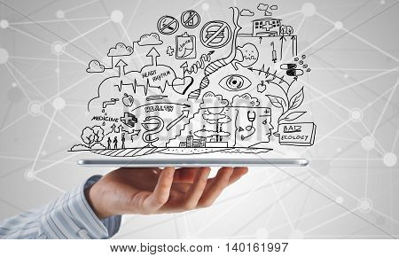 Close view of businessman showing tablet pc with sketched medicine concept