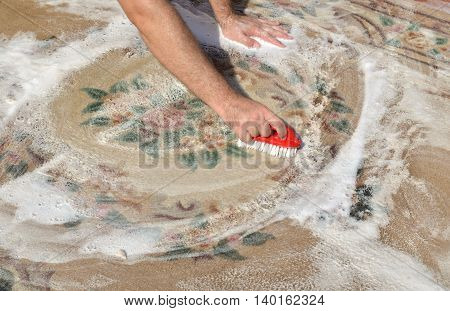 Washing carpet outside with red brush and soapy water on a sunny day