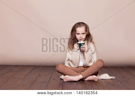 a little girl sitting on the floor and drinking tea