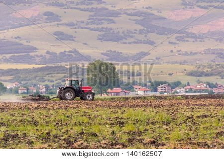Red tractor ploughing field in summer days