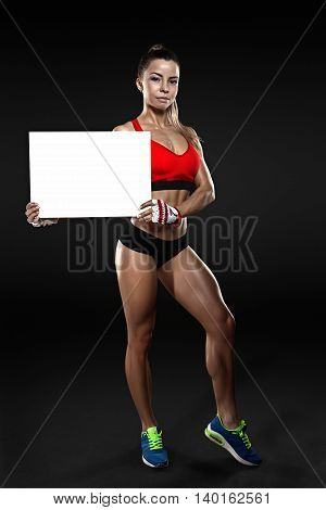 Young fitness female holding a blank sign ower dark background, isolated with clipping path