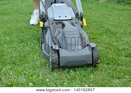 Closeup of lawn mower which is pushed by a man during trimming grass