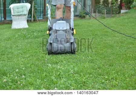 Man is pushing a mower to cut grass in his garden