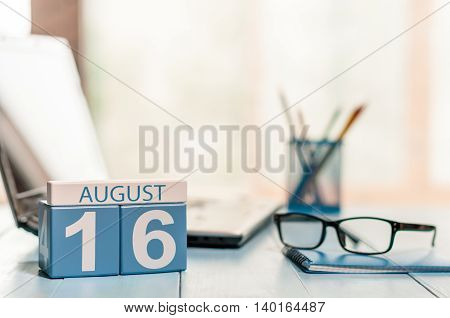 August 16th. Day 16 of month, wooden color calendar on office workplace background. Summer time. Empty space for text.