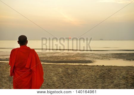 Buddhist monk standing on the beach and watching the sunrise