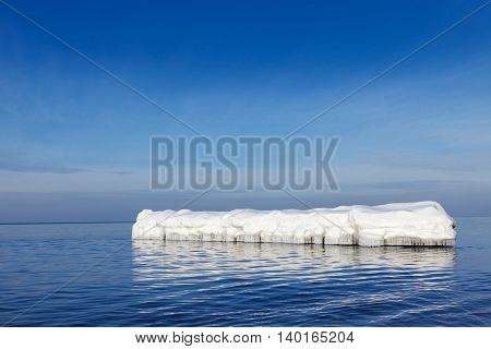 the breakwater in the form of an iceberg in a Sunny winter day