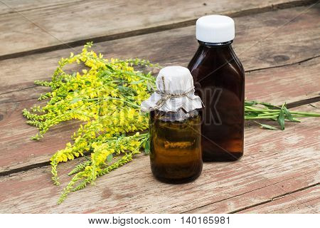 Melilotus officinalis known as yellow sweet clover yellow melilot ribbed melilot common melilot and pharmaceutical bottles on old wooden table. Used in herbal medicine is a major source of nectar