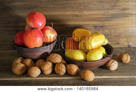 apples pears and walnuts on a wooden background