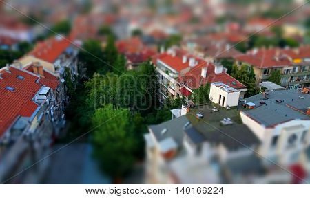 Toy like miniature tilt-shift effect photo of a residential housing top roof terraces and trees in-between the buildings