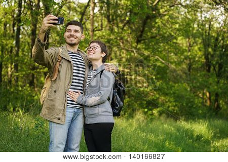 couple man and woman with backpacks in the forest sends image to your phone in social networks.