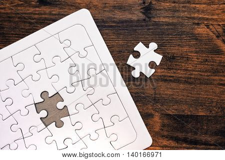 Jigsaw puzzle with one missing piece left to complete copy space top view