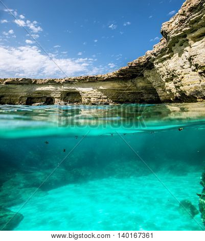 View of the cliffs and sea caves of Cape Greco from under the water and above the water.Cyprus