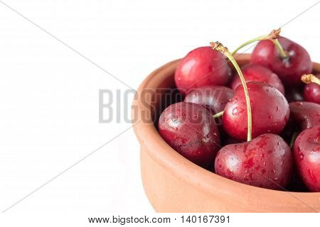 Isolated Cherries in a brown bowl on the white background