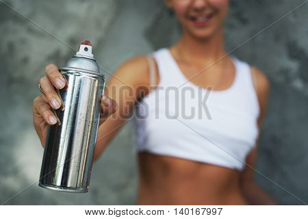 Girl with spray paint in hand against the background of a gray wall. Bottle of paint in focus.