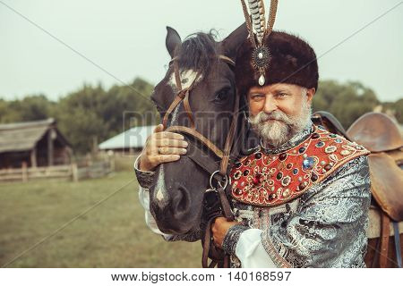 King Dressed In Medieval Costume Is Stroking His Horse On The Rural Summer Background.