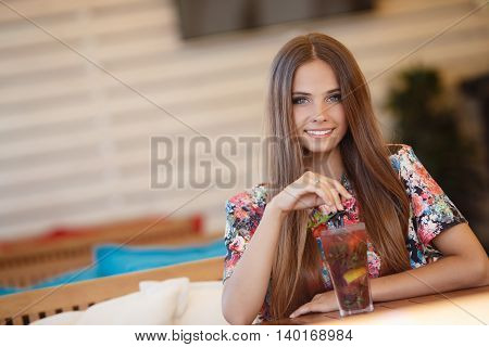Portrait of beautiful young woman with gray eyes and long straight brown hair,nice smile,light makeup,wearing jewelry,wearing a colored blouse,sits alone at a table in a cafe with a glass of fruit cocktail