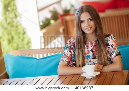 Portrait of beautiful young woman with gray eyes and long straight brown hair,nice smile,light makeup,wearing jewelry,wearing a colored blouse,sits alone at a table in a summer cafe with a white Cup of hot coffee latte