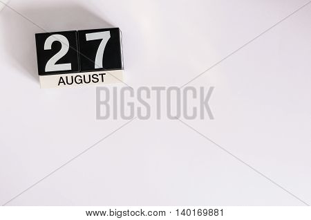 August 27th. Image of august 27 wooden color calendar on blue background. Summer day. Empty space for text.