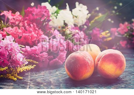 Summer ripe red peach fruits on the rustic wooden board with colorful flowers, organic eco local food natural concept in hipster style