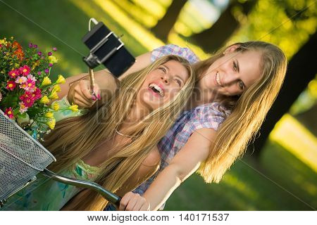 Two beautiful females taking photo of themselves with smartphone by using selfie stick in nature. Fun, youth and lifestyle concepts.