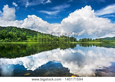 Beautiful landscape with cloudy blue sky reflected in the clear river water. Wooded waterside of a mountain lake. Summer idyllic landscape.