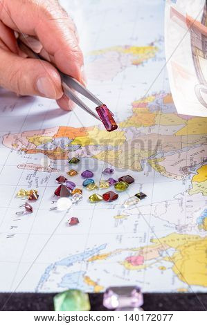Dealer in precious stones do business on his desk. Payment gemstone in Euro.