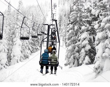 Skiers on a Colorado ski resort lift ride