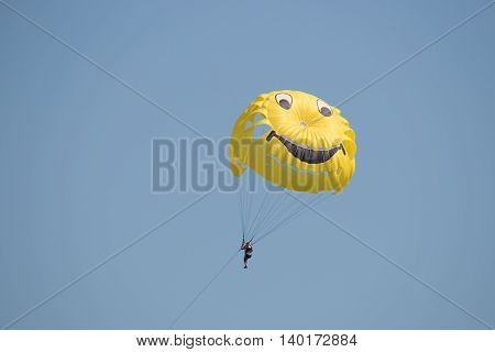 Man flying high on a colored parachute at sunrise