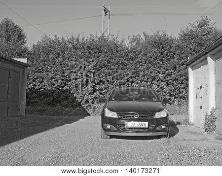 2016/07/09 Kadan Czech republic - black car parked between garages
