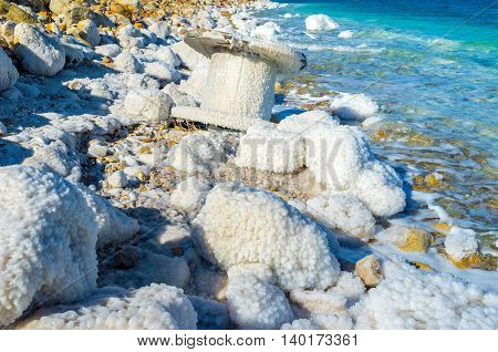 All the stones and objects on the Dead Sea shore are covered with the crystals of the dried salt Ein Gedi Israel.