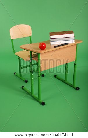 New school desk and chair on green background