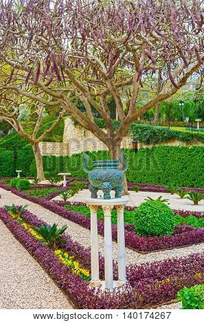 The Oriental vase on three slender pillars in the flower bed of Bahai Garden Haifa Israel.