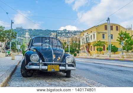 HAIFA ISRAEL - FEBRUARY 20 2016: The vintage black car is parked in Ben Gurion Boulevard and surrounded by old houses of German Colony on February 20 in Haifa.