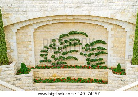 The decorative wall of Bahai Gardens with the flower beds and tiny trimmed trees Haifa Israel.