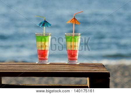 Multi-colored cocktails on a wooden table in the background on the beach and sea