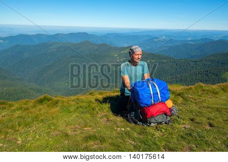 Hiker sitting on a mountain pass rest admiring nature and adjusts equipment. Trekking in the Ukrainian mountains
