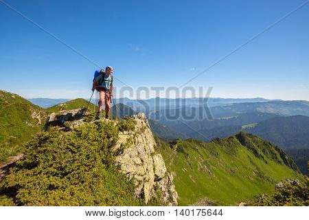 Backpacker standing on a rock over the cliff and looking down into the valley. Carpathian mountains. Ukrainian Marmarosy